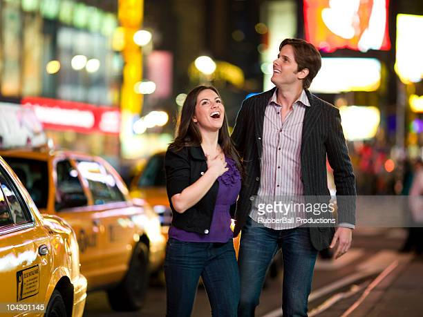 USA, New York, New York City, Manhattan, Times Square, young couple lauhing in street