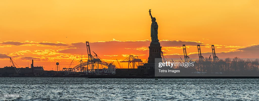 USA, New York, New York City, Silhouette of Statue of Liberty at sunset : Stock Photo