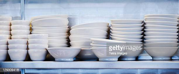 USA, New York, New York City, Stacked plates and bowls in kitchen