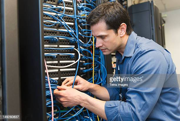 USA, New York, New York City, Technician inspecting network server