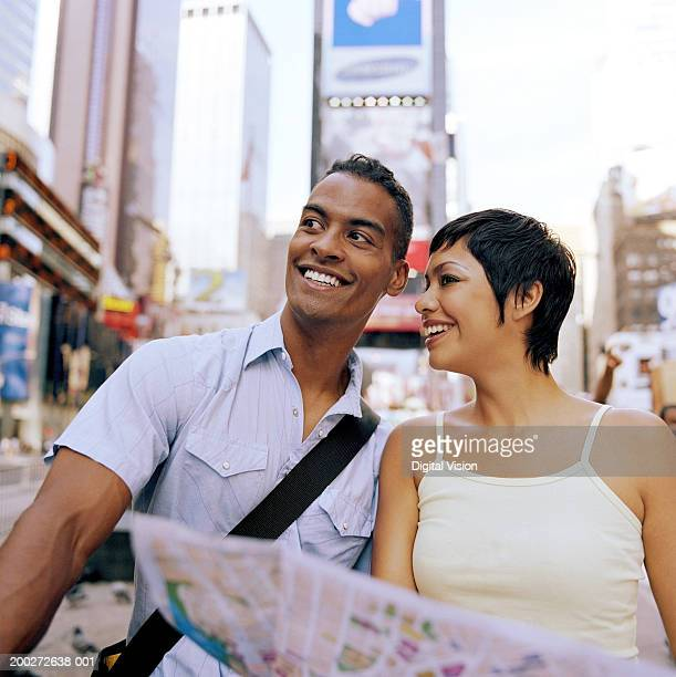 USA, New York, New York City, young couple holding map in Times Square