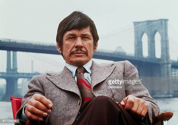 Publicity handout from Death Wish shows Charles Bronson seated on the banks of the East River with the Brooklyn Bridge in the background 1974