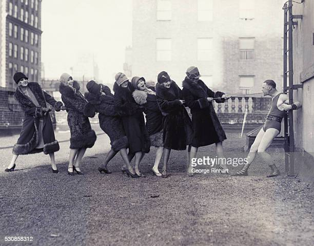 New York NY Andre Reverdy the World's strongest man at his weight 115 pounds outpulls a bevy of beauties of the Earl Carroll's 'Vanities' on the roof...