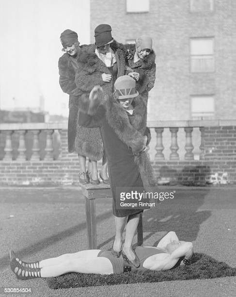 New York NY Photo shows Andre Reverdy world's strongest man at his weight 115 pounds give his version of 'Old Ironsides' by allowing Miss Irma...