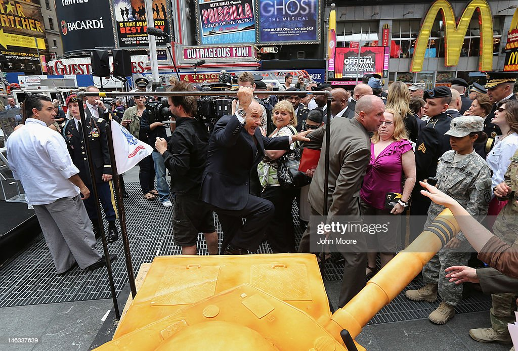 New York Police Commissioner Ray Kelly skirts a giant cake after attending a ceremony marking the U.S. Army's 237th anniversary on June 14, 2012 in Times Square in New York City. U.S. Army Chief of Staff Gen. Raymond Odierno cut the cake before swearing in16 new recruits during the event. ''Cake Boss'' reality show Buddy Valastro (L), helped Odierno cut the 500 pound cake in the shape of a tank, which Valastro said took eight of his staff three days to prepare for the event.