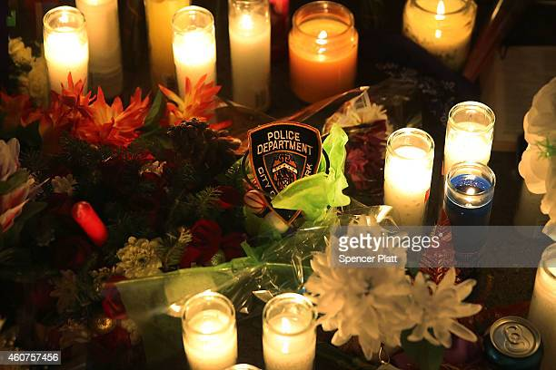 New York Police Department badge is placed among candles and flowers at a makeshift memorial for two New York City police officers at the location...