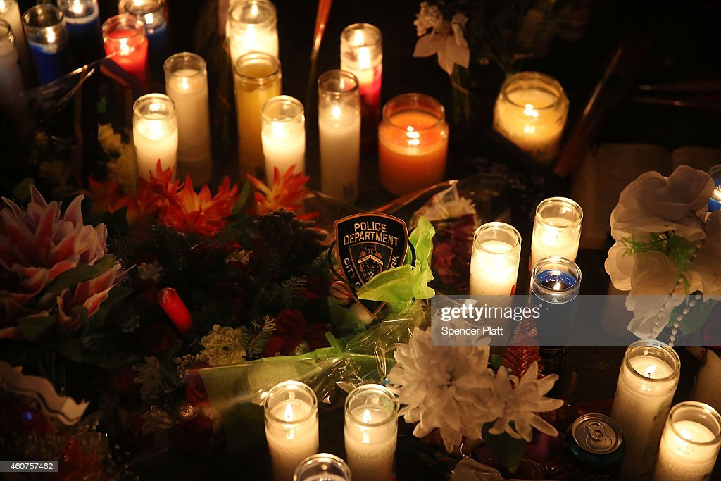 New York Police Department bagge is placed among flowers and candles at a makeshift memorial for two New York City police officers at the location...