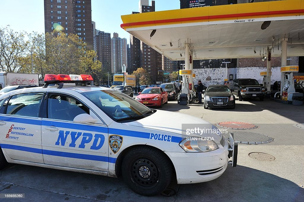 A New York Police Department car guards a Shell gasoline station on November 9 2012 in New York as New York City begins to ration gas according to...