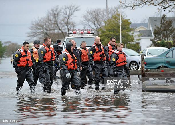 New York Police Department divers walk through a flooded area on October 30 2012 in the Breezy Point area of Queens in New York that was hit hard by...