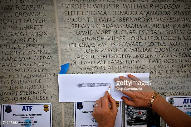 New York Police Department employee Evelyn Sekzer makes a rubbing of a name carved into the wall at the National Law Enforcement Officers Memorial...
