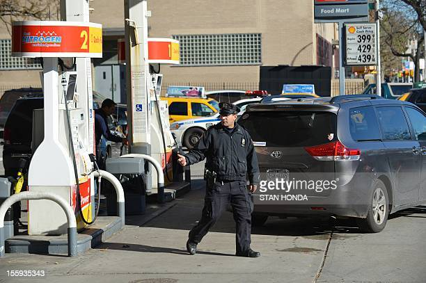 A New York Police Department officer directs cars at a Shell gasoline station on First Avenue and East 96th Street on November 9 2012 in New York as...