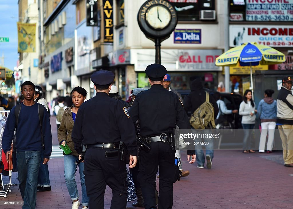 New York Police Department officers patrol around Jamaica Avenue and 162nd street in Queens on October 24 one day after a hatchet attack on NYPD...