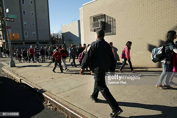 New York Police Department officers stand guard in front of the Peter Rouget Brooklyn middle school as children are let back in following reports of...