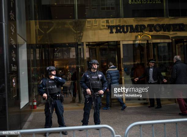 New York Police Department security officers stand outside as tourists and curiosity seekers visit Trump Tower along Fifth Avenue February 25 2017 in...