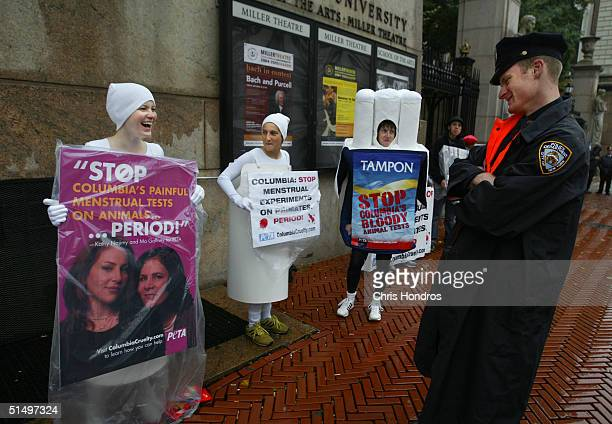 New York Police officer smiles as he looks over the tampon outfit of a People for the Ethical Treatment of Animals activist outside of Columbia...