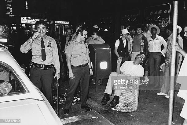 New York police officers find a man sitting in a litter bin in Times Square New York City 1976
