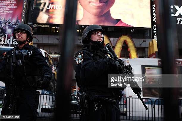 New York police officers with high powered rifles patrol in Times Square on December 7 2015 in New York City Following a series of mass shootings in...