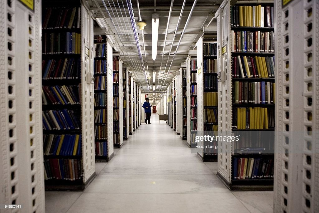 New York Public Library staff member walks between aisles of books stored in an area known as the 'stacks' under Bryant Park adjacent to the...