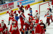 New York Ranger fans dressed as Santa Clause mock the Islanders fans in the first period intermission during the Philadelphia Flyers and New York...