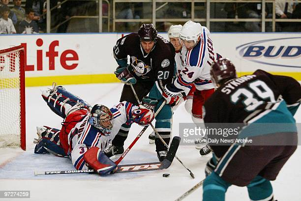 New York Rangers' goalie Dan Blackburn dives to make the save as teammate Sylvain Lefebvre tries to tie up Anaheim Mighty Ducks' Steve Rucchin The...