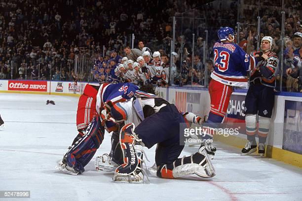 New York Rangers goalie Dan Cloutier pummels New York Islander Tommy Salo while Ranger defenseman Jeff Beukeboom grabs Islander JJ Daigneault by the...