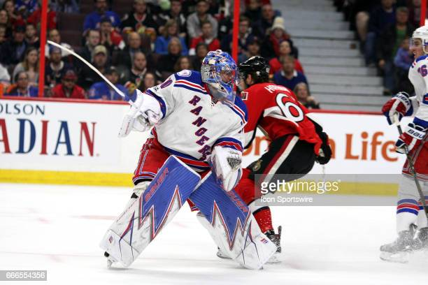 New York Rangers Goalie Henrik Lundqvist clears the puck with Ottawa Senators Left Wing Mike Hoffman moving in during the second period in a game...