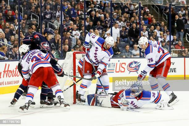 New York Rangers goalie Henrik Lundqvist falls to the ice to defend multiple shots and is assisted by four other Rangers during the third period in a...