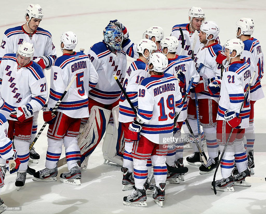 New York Rangers teammates surround goaltender Henrik Lundqvist #30 following the team's victory over the Carolina Hurricanes at PNC Arena on April 6, 2013 in Raleigh, North Carolina.