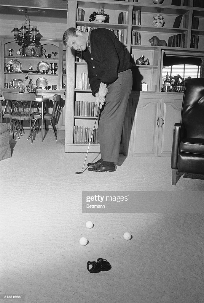 New York slugger Mickey Mantle kept from the golf course by his ailing shoulder keeps his putting touch tuned by practicing in the den of his home...
