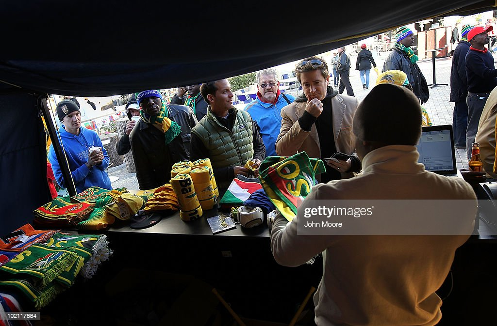 New York soccer fans Eliot Relles (C), and Peter Friedman (R) buy South African soccer paraphernalia at a World Cup match viewing area on June 15, 2010 in Johannesburg, South Africa. Despite freezing temperatures fans came out to watch the matches.