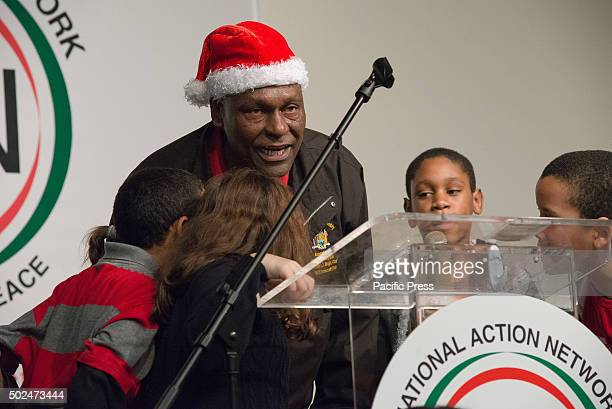 New York State Assemblyman Keith Wright leads a group of children in wishing the attendees of the holiday meal 'Happy Holidays' New York City Mayor...