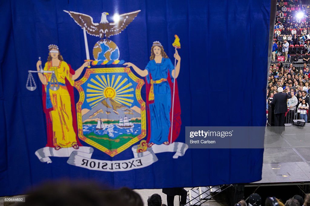 A New York state flag hangs in front of democratic presidential candidate Bernie Sanders as he speaks at a rally for his campaign on April 11, 2016 in Binghamton, New York. The New York Democratic primary is scheduled for April 19th.