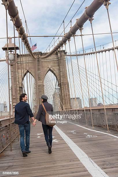 USA, New York State, New York City, Brooklyn, Couple holding hands and walking on Brooklyn Bridge