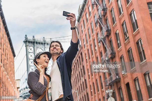 USA, New York State, New York City, Brooklyn, Couple taking selfie on street, Brooklyn Bridge in background
