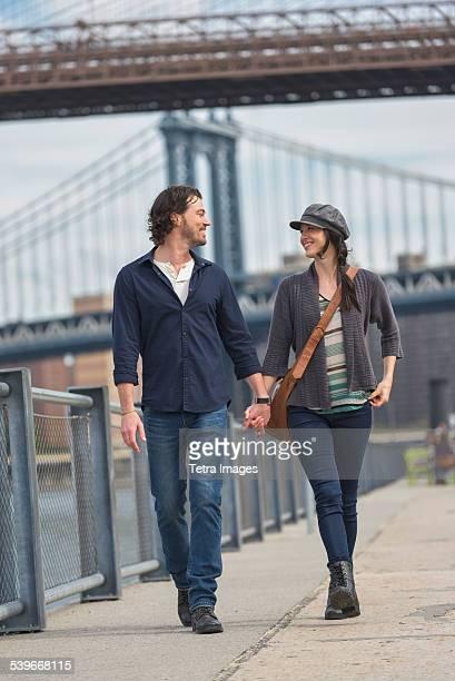 USA, New York State, New York City, Brooklyn, Couple walking on promenade, Brooklyn Bridge in background