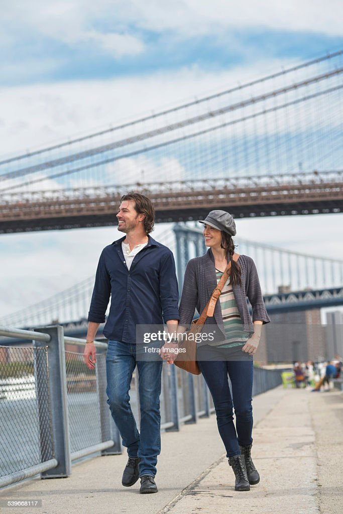 USA, New York State, New York City, Brooklyn, Couple walking on promenade, Brooklyn Bridge in background