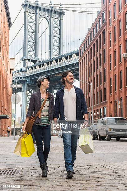 USA, New York State, New York City, Brooklyn, Couple walking on street, Brooklyn Bridge in background