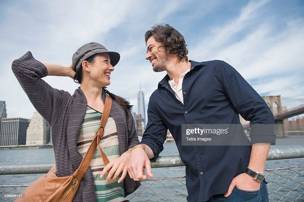 USA, New York State, New York City, Brooklyn, Happy couple standing and leaning against railing