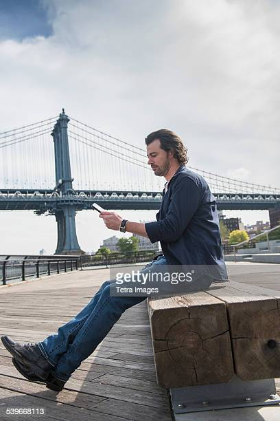 USA, New York State, New York City, Brooklyn, Man using tablet pc, Manhattan Bridge in background