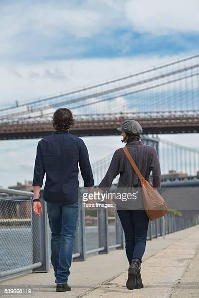 USA, New York State, New York City, Brooklyn, Rear view of couple walking on promenade, Brooklyn Bridge in background