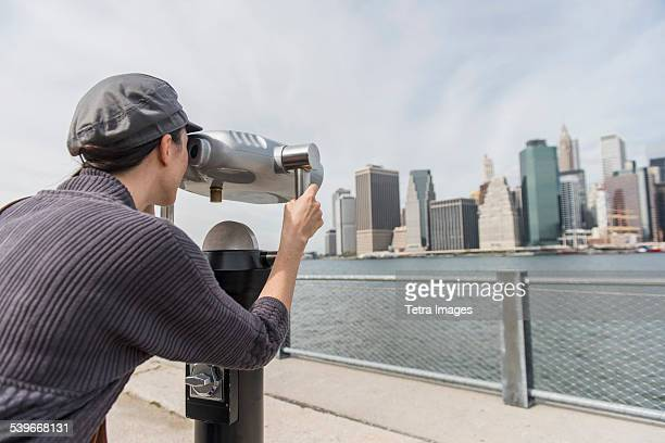 USA, New York State, New York City, Brooklyn, Woman watching cityscape through coin-operated binoculars