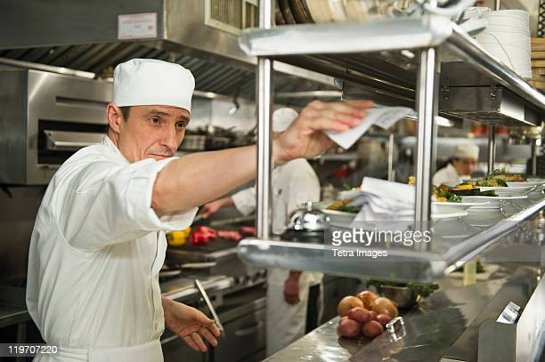 USA, New York State, New York City, Chef putting order on stick, in background chefs preparing food