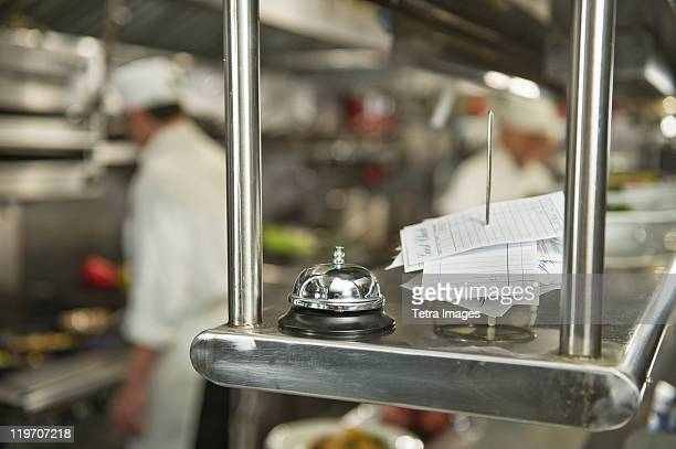 USA, New York State, New York City, Chefs preparing food in kitchen, focus on service bell on foreground