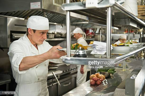 USA, New York State, New York City, Chefs preparing food in kitchen