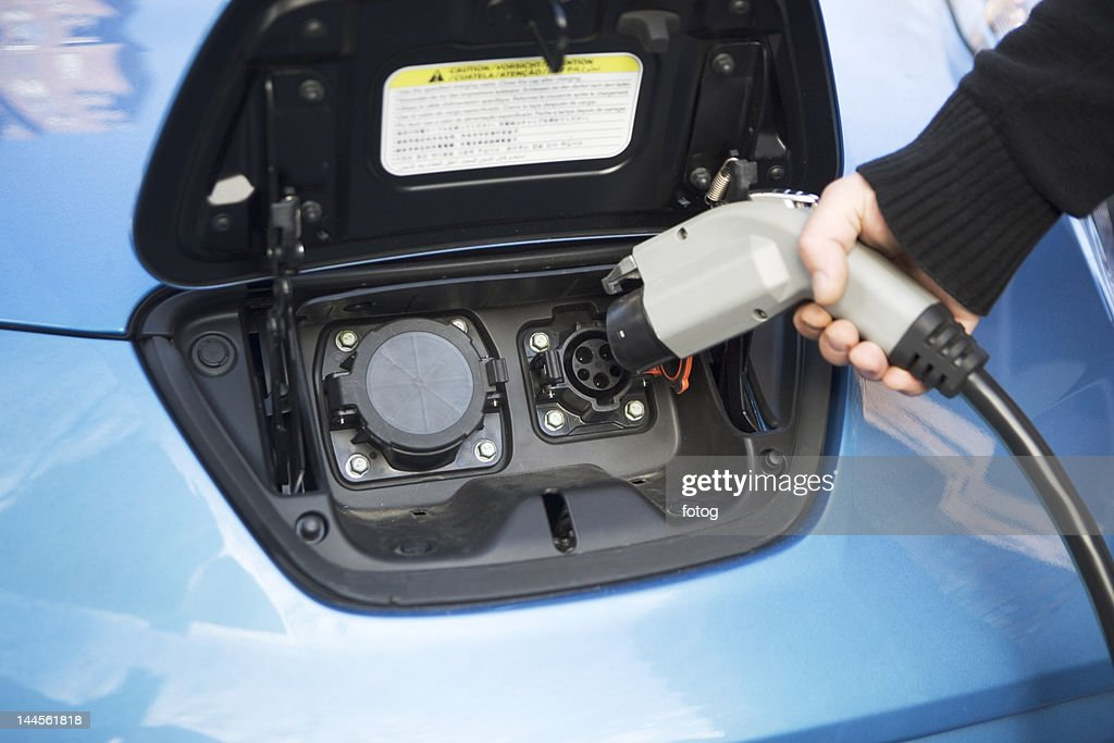 USA, New York State, New York City, close-up of man charging electric car