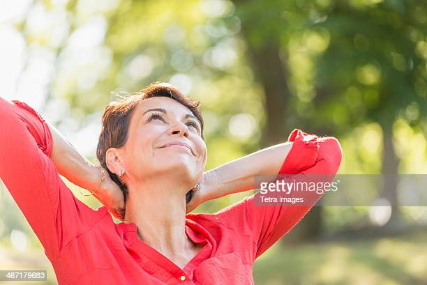 USA, New York State, New York City, Happy mature woman raising hands in park