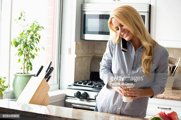 USA, New York State, New York City, Long Island City, Happy woman talking on mobile phone in kitchen