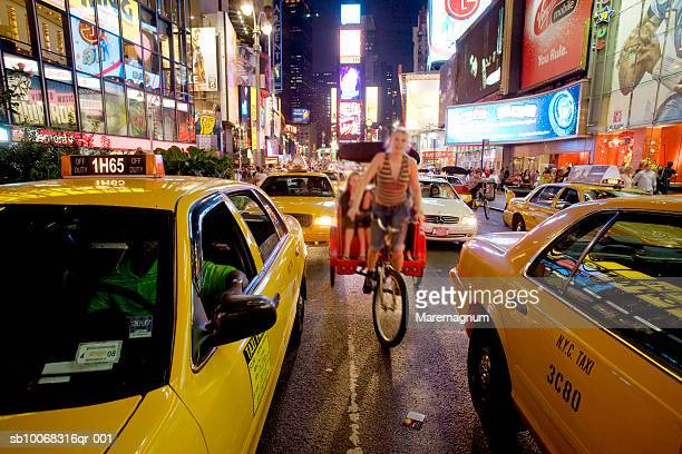 USA, New York State, New York City, Manhattan, rickshaw driver riding between yellow cabs in street