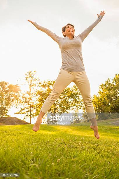 USA, New York State, New York City, Mature woman jumping on grass