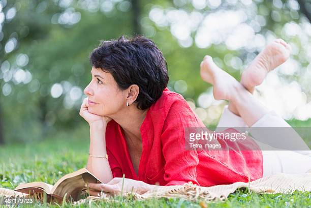 USA, New York State, New York City, Mature woman lying on grass and reading book